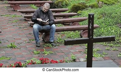 Man on bench with the Bible at outdoors church