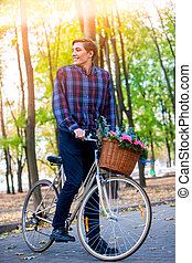 Man on bicycle with flowers basket is riding summer park .