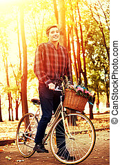 Man on bicycle with flowers basket is riding summer park.