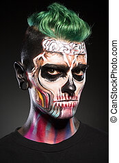 Man on black background with colored skull makeup.