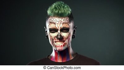 Man on black background with colored skull makeup. -...