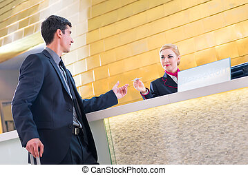 Man on business trip at hotel reception