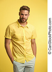 Man on calm face posing confidently with hands in pockets. Man look attractive in casual linen shirt. Guy fashion model wear casual shirt. Feel comfortable in simple outfit. Casual comfortable outfit