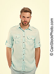 Man on calm face posing confidently with hands in pockets, white background. Guy with bristle wears casual or formal shirt. Fashion concept. Man looks attractive in casual linen blue shirt
