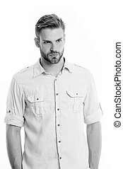 Man on calm face posing confidently with hands in pockets, white background. Man looks attractive in casual linen shirt. Guy with bristle wears casual or formal shirt. Fashion concept