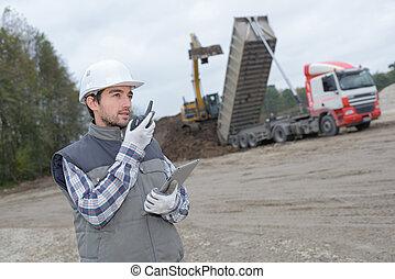 Man on construction site talking into walkie talkie