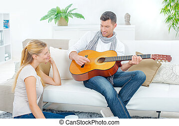 Man on couch, playing guitar to lady