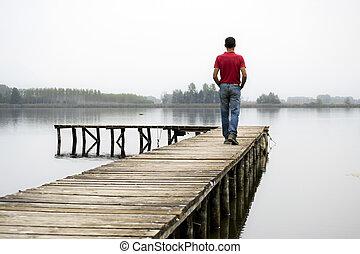 man on dock - man walking on a wooden dock on lane