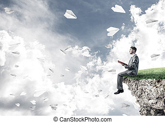 Man on edge reading book and paper planes flying in air