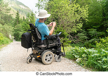 man on electric wheelchair using smartphone camera in nature