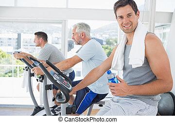 Man on exercise bike holding water bottle