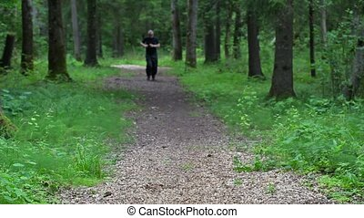 Man on forest trail slowly run