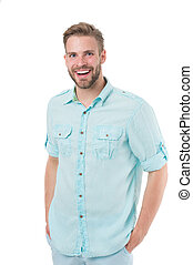 Man on happy smiling face posing confidently with hands in pockets, white background. Man looks attractive in casual linen blue shirt. Guy with bristle wears casual or formal shirt. Fashion concept