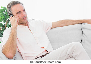 Man on his couch on the phone