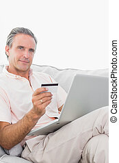 Man on his couch using laptop for shopping online smiling at camera at home in living room