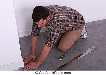Man on his knees fitting a grey linoleum floor