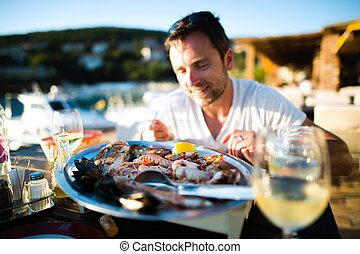 Man on holiday, sitting outside at sunset, eating seafood