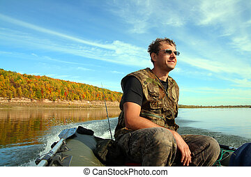 man on inflatable boat with motor - fishing man on ...