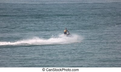 Man on jet ski. Summer water extreme. Lifeguard on a water scooter. Entertainment at sea.