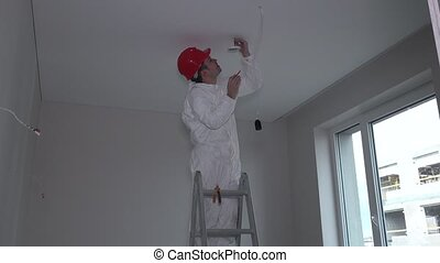 Man on ladder installing smoke detector on room ceiling....