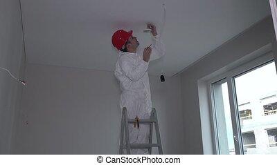 Man on ladder installing smoke detector on room ceiling