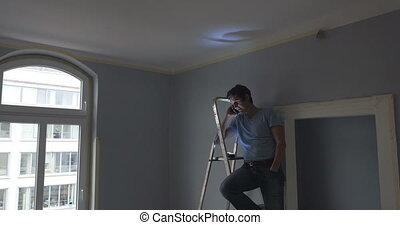 man on ladder making phone call