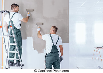 Man on ladder painting wall