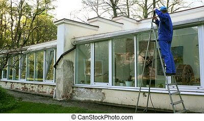 Man on ladder with high pressure washing tool clean glass house in nature.