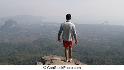 Man On Mountain Top Raise Hands Looking At Beautiful...