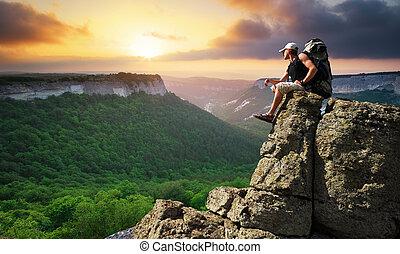 Man on peak of mountain