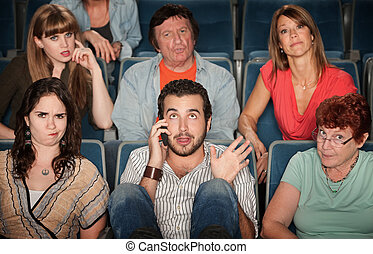 Man On Phone In Theater - Young man on phone disturbs people...