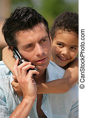 man on phone with little metis boy