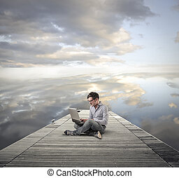 Man on pier with laptop