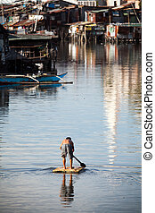 Man paddling down river on makeshift raft. Heavily polluted Paranaque River, Manila, Philippines. Squatter / Shanty housing lining the river banks.
