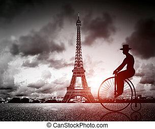 Man on retro bicycle next to Effel Tower, Paris, France....