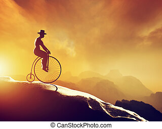 Man on retro bicycle riding downhill. Mountains scenery