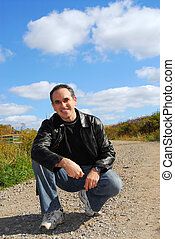 Man on road - Smiling man sitting on a country road