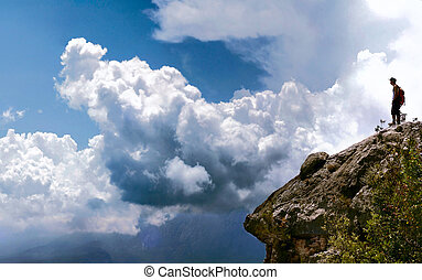 Man on rock in clouds