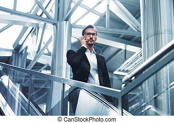 Man on smart phone - young businessman in airport. Handsome serious men wearing suit jacket indoors