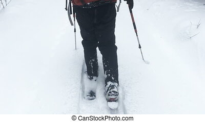 Man on snowshoes walking on white snow. Close up footage of...