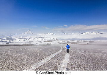man on snowy field in kamchatka mountains near covered by snow volcanoes