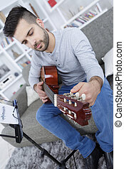 man on sofa playing the guitar at home