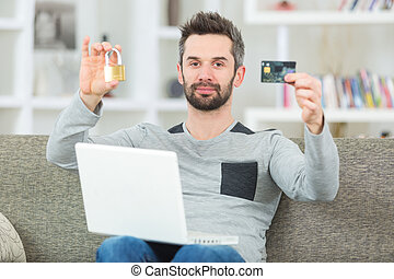 man on sofa with laptop holding bank card and padlock