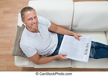 Man On Sofa With Newspaper
