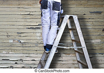 man on stepladders - Legs of man in white stained overalls...