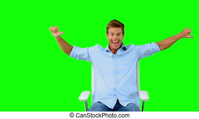 Man on swivel chair giving thumbs up on green screen in slow...