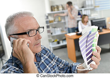 man on telephone with color samples