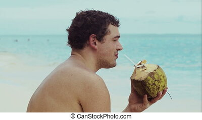 Man on the beach drinking from coconut