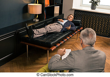 Man on the couch talking to a psychotherapist