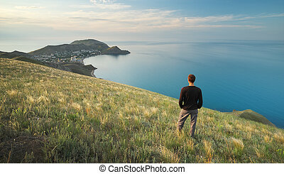 Man on the edge. Cliff of mountain and sea. Conceptual...